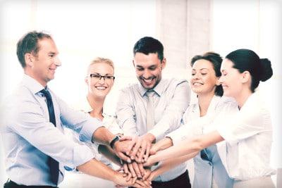 Mitarbeiter im Büro legen Hände übereinander als Symbol von einer Einheit