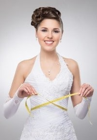 Hochzeitsbraut im Hochzeitskleid mit Maßband in der Hand