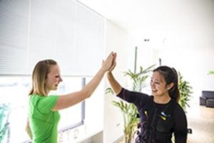 Slim-Gym Trainerin motiviert glückliche junge Frau
