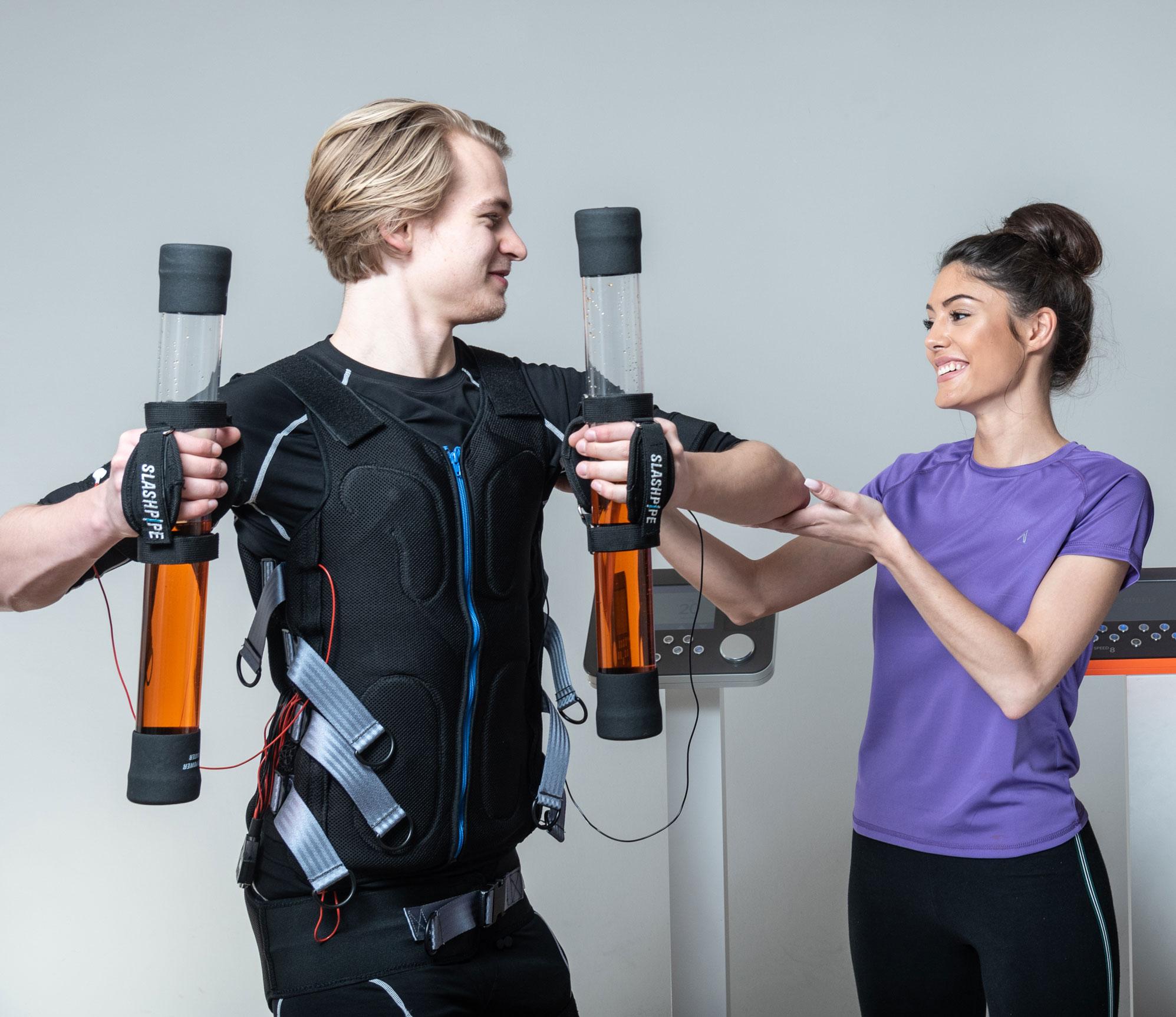 Trainerin unterstützt beim EMS Training zum Muskelaufbau.